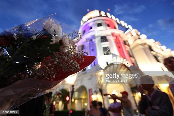 TOPSHOT People look at the Negresco Palace illuminated with the colours of the French National flag in tribute for the victims of the deadly Bastille...