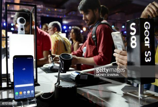People look at the newly launched Samsung Galaxy S8 and Galaxy S8 smartphones during an event in New Delhi on April 19 2017 / AFP PHOTO / MONEY SHARMA