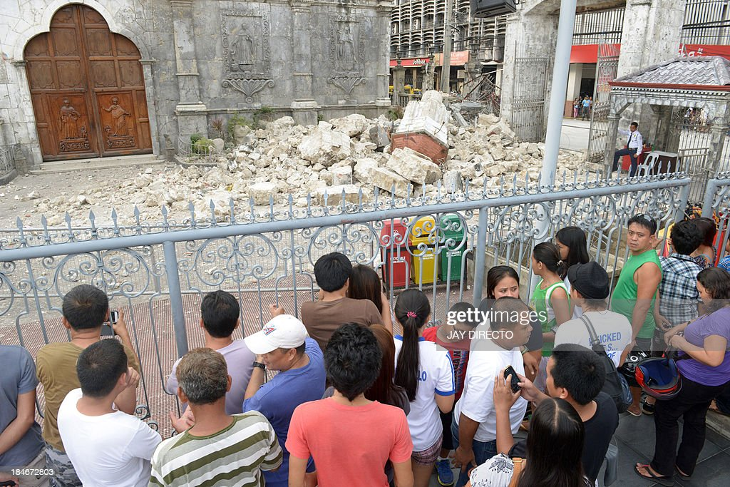 People look at the ruins of Basilica Minore del Santo Nino bell tower following a 7.1-magnitude quake in Cebu on October 15, 2013. A powerful earthquake killed at least 73 people on October 15 as it tore down modern buildings, destroyed historic churches and triggered terrified stampedes across popular tourist islands in the Philippines. AFP PHOTO / Jay DIRECTO