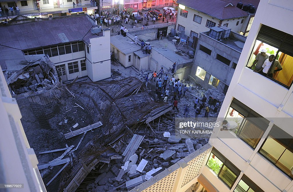 People look at the scene of a building collapse on January 16, 2013 at Kenya's lakeside town of Kisumu killing at least three people. The building that was still under construction is suspected to have caved in on itself due to the failure of the site's contractors to adhere to appropriate standards of construction. AFP PHOTO/Tony KARUMBA