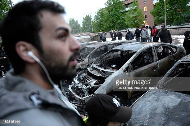 People look at the scene where cars stand gutted by fire in the Stockholm suburb of Rinkeby after youths rioted in several different suburbs around...