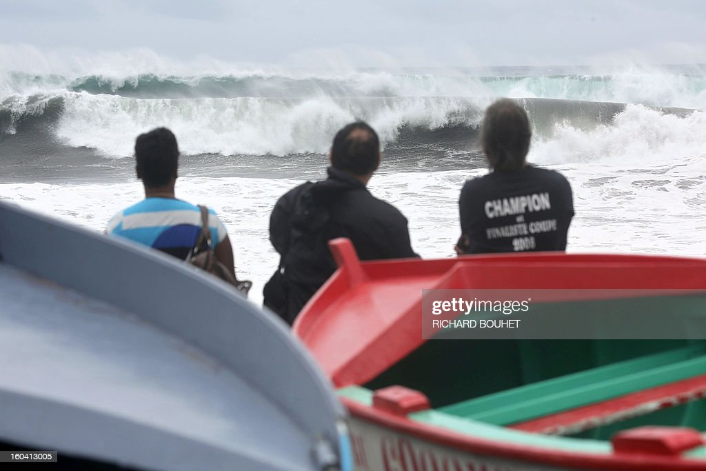 People look at the sea on the northwestern coast of French Indian Ocean island of La Reunion on January 31, 2013 near Saint-Paul, as high waves hit the coastline, caused by the cyclone Felleng at 530 Km north of the island. BOUHET