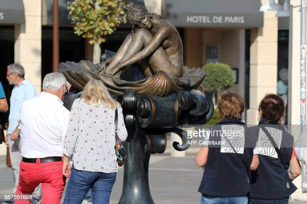 People look at the statue of French actress Brigitte Bardot based on an illustration watercolour by Italian illustrator Milo Manara at the Riviera...