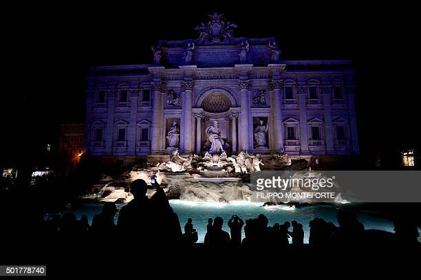 TOPSHOT People look at the the 18thcentury Baroquestyle fountain of Trevi lighted with colors on December 17 2015 as part of Rome's canditature for...
