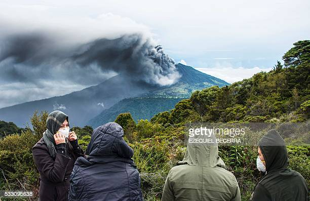 TOPSHOT People look at the Turrialba volcano as it spewes ashes on May 20 in Cartago Costa Rica The Turrialba volcano started erupting columns of...