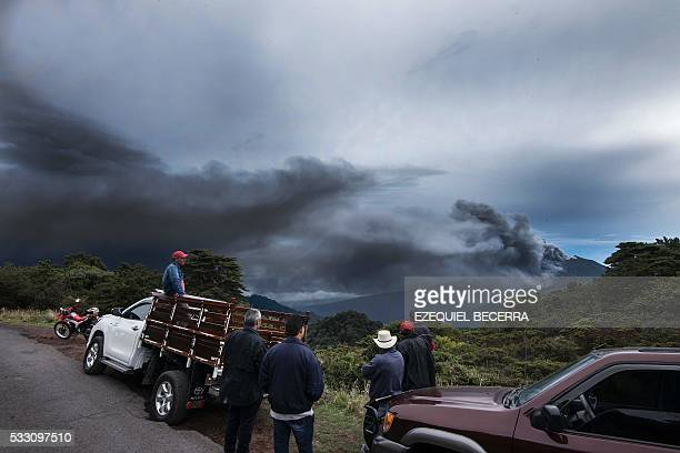 People look at the Turrialba volcano as it spewes ashes on May 20 in Cartago Costa Rica The Turrialba volcano started erupting columns of smoke and...