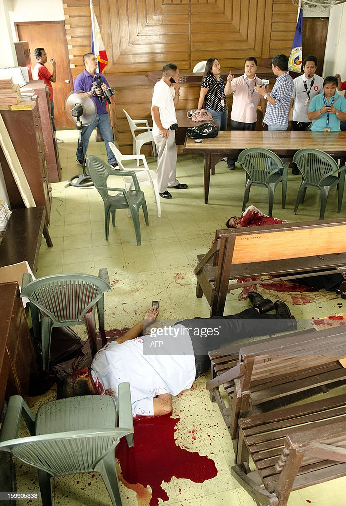 People look at the two dead bodies lying on the floor, shot by a Canadian national inside a court room, in Cebu City, central Philippine on January 22, 2013. A Canadian man shot dead two people including a lawyer in a Philippines courtroom January 22, using a pistol he smuggled inside the court as he went on trial for petty mischief, police said.