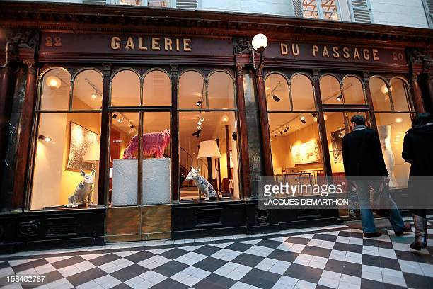 People look at the window of an art gallery on December 15 2012 in Paris in the 'Galerie VeroDodat' located between Bouloi and JeanJacques Rousseau...