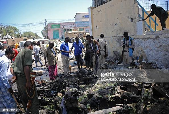 People look at the wreckage of a car bomb outside the Education Ministry in Mogadishu on April 14 2015 Somalia's AlQaedalinked Shebab militants on...