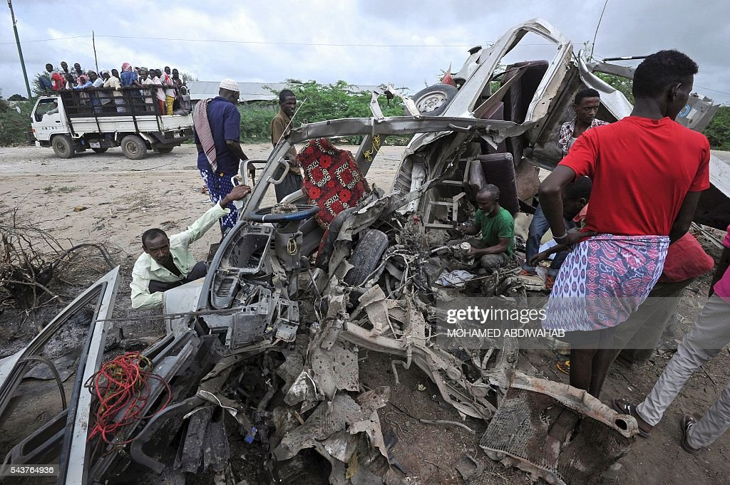 People look at the wreckage of a minibus ripped by a bomb on June 30, 2016, in Afgooye. A roadside bomb ripped apart a minibus just outside Somalia's capital Mogadishu on Thursday, killing at least eight people and injuring several others, a witness said. 'There was a terrible incident, a landmine hit a civilian minibus,' said Mohamed Wedow, a witness at the scene near the town of Afgooye. 'At least eight people died and more than 20 others were wounded in the blast.' ABDIWAHAB