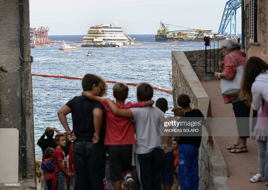 People look at the wreckage of Italy's Costa Concordia cruise ship which begins to emerge from water on September 17, 2013 near the harbour of Giglio Porto. Salvage operators in Italy lifted the Costa Concordia cruise ship upright from its watery grave off the island of Giglio in the biggest ever project of its kind. The ship's horn sounded for the first time since the January 13, 2012 tragedy, its sound mixing with applause and cheers in the port in a dramatic climax to the massive salvage operation. Local residents and survivors spoke of an eerie feeling as the ship rose, saying the sight reminded them of the tragedy that claimed 32 lives.