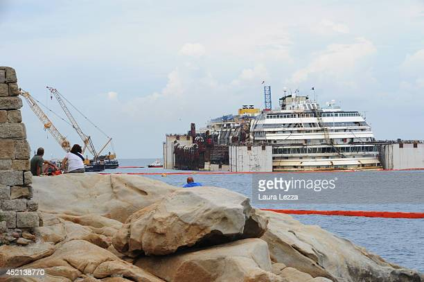 People look at the wrecked ship Costa Concordia during the refloating operations on July 14 2014 in Isola del Giglio Italy On the first day of the...
