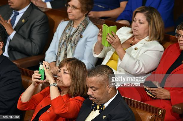 People look at their cell phones as Pope Francis addresses the joint session of Congress on September 24 2014 in Washington DC The Pope is the first...