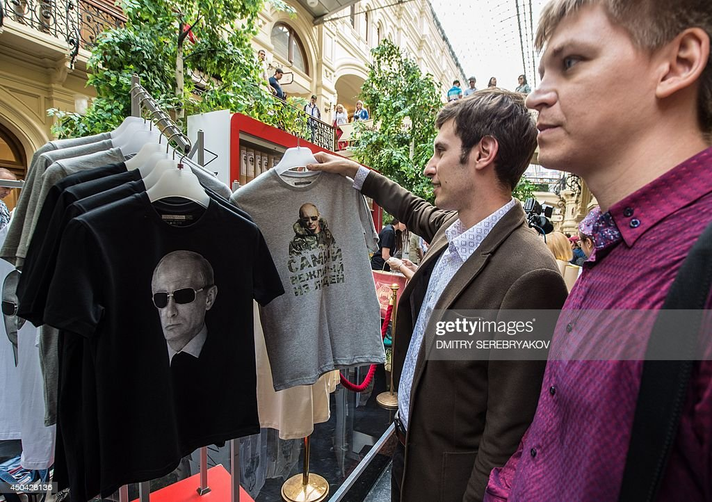 People look at T-shirts with images of Russia's President Vladimir Putin being displayed for sale at GUM, one of the oldest department stores in central Moscow, on June 11, 2014.