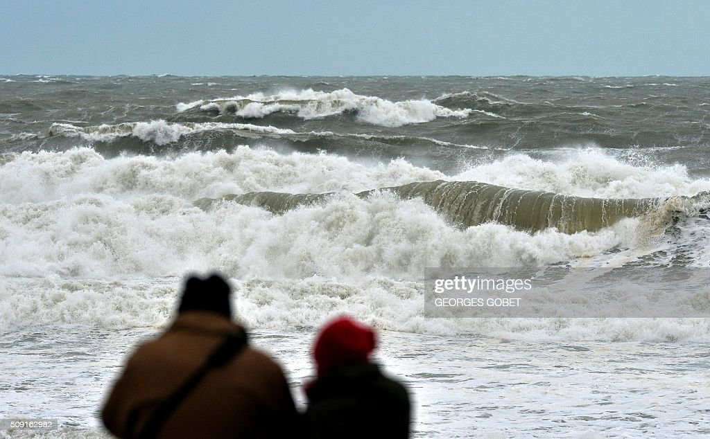 People look at waves at the Lacanau beach, western France, on February 9, 2016. France's Atlantic coast was lashed by powerful waves and authorities in resorts such as Biarritz took hasty measures to try to prevent the sea reaching the town. High winds buffeted northwestern Europe on February 8, leaving one woman in France in a coma after she was hit by an advertising hoarding. GOBET