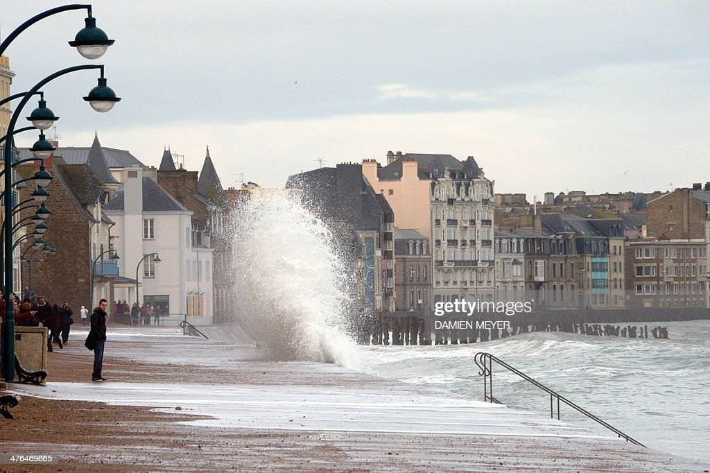 People look at waves crashing against the seawall on the coast of SaintMalo western France on March 3 2014 Due to high tides scheduled late today 11...