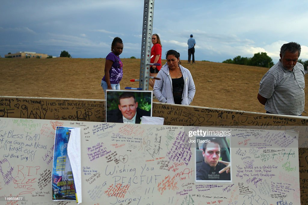 People look at what visitors have written on poster boards at a memorial setup across the street from the Century 16 movie theatre on July 30, 2012 in Aurora, Colorado. Twenty-four-year-old James Holmes is suspected of killing 12 and injuring 58 others during a shooting rampage at the theater during a screening of 'The Dark Knight Rises.'