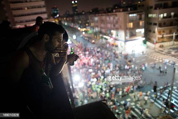 People look down from a balcony as demonstrators march through the streets to protest against Israeli Finance Minister Yair Lapid's budget cuts on...