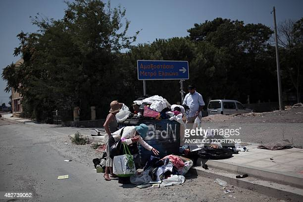People look for used clothes at a rubbish bin in a street market near in Athens on August 2 2015 AFP PHOTO / ANGELOS TZORTZINIS