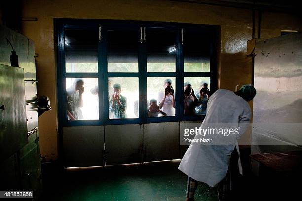 People look in as a Kashmir government employee works inside a chicken hatchery on August 03 2015 in Srinagar the summer capital of Indian...