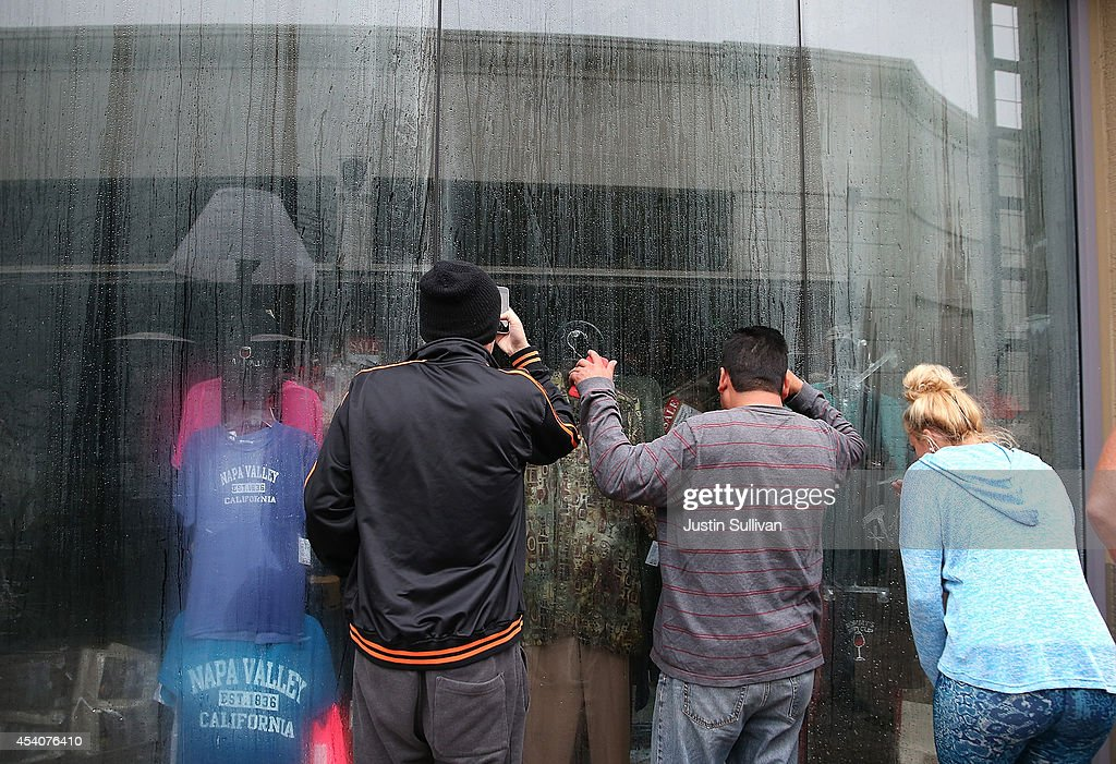 People look in the window of a business that is flooded by a broken water main following a reported 6.0 earthquake on August 24, 2014 in Napa, California. A 6.0 earthquake rocked the San Francisco Bay Area shortly after 3:00 am on Sunday morning causing damage to buildings and sending at least 70 people to a hospital with non-life threatening injuries.