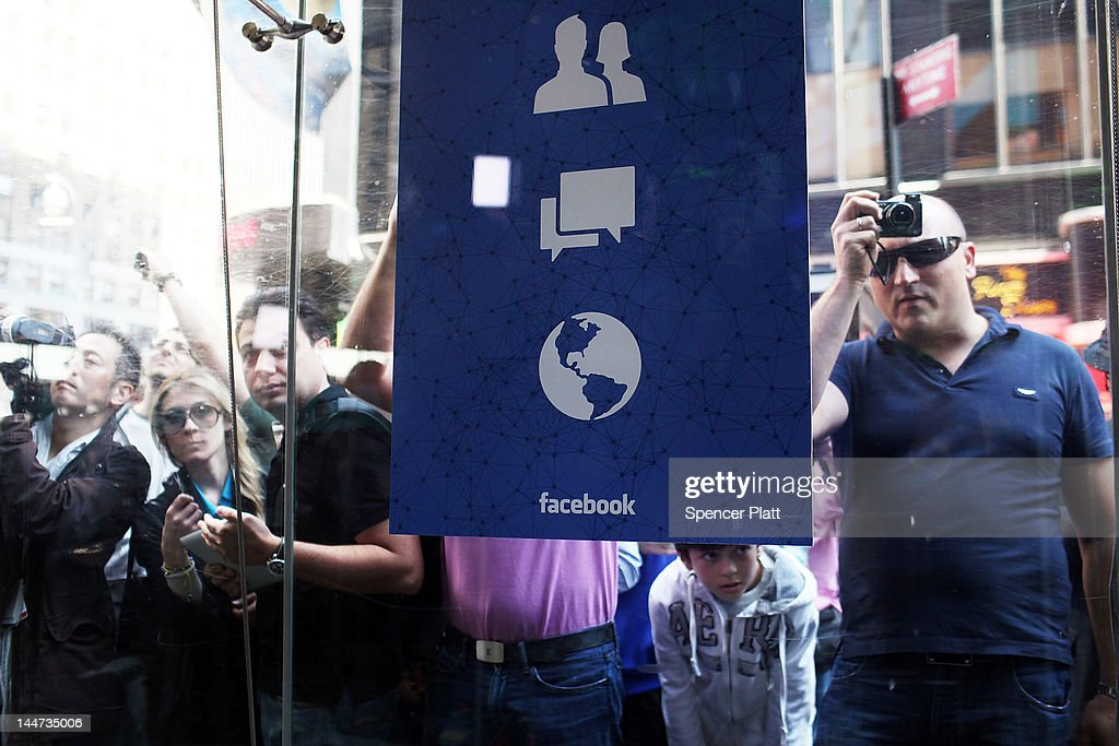 People look into the window of the Nasdaq stock market moments before Facebook shares went public on May 18, 2012 in New York, United States. The social network site began trading after 11:30 a.m. with shares jumping 13% to $43 before quickly falling. On Thursday Facebook priced 421 million shares at $38 each. Facebook, a Menlo Park, California based company, will have a valuation exceeding $100 billion.Ê