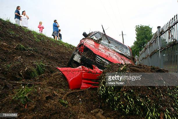 People look on as a car lies down an embankment after being washed off the road by a flash flood at Broughton Anglican College in Campbelltown on...