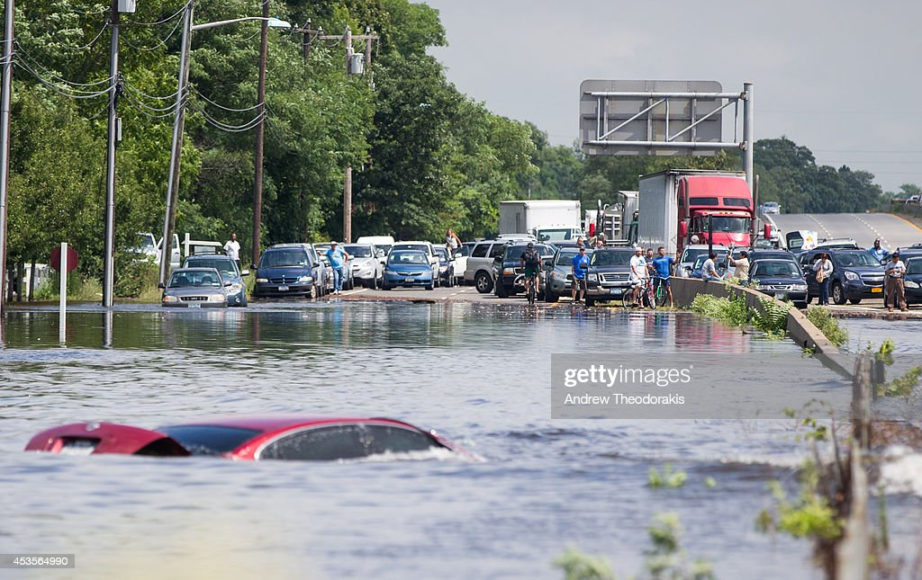 People look on as a car remains flooded on Sunrise Highway at Route 111 following heavy rains and flash flooding August 13, 2014 in Islip, New York. The south shore of Long Island along with the tri-state region saw record setting rain that caused roads to flood entrapping some motorists.