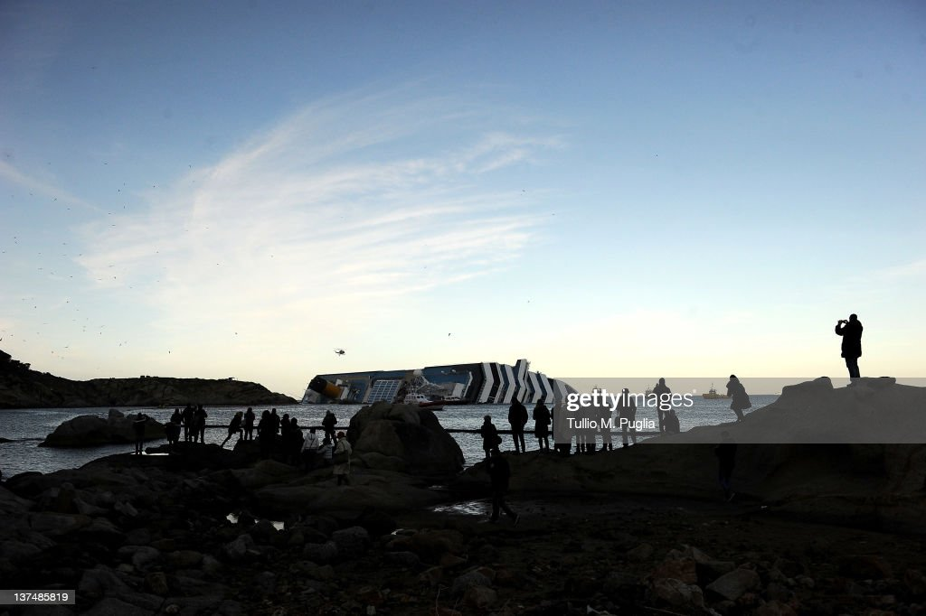 People look on as Cruise ship Costa Concordia lies stricken off the shore of the island of Giglio on January 21, 2012 in Giglio Porto, Italy. The body of a woman was recovered by Italian coast guard divers from the capsized cruise ship Costa Concordia, raising the death toll to 12.