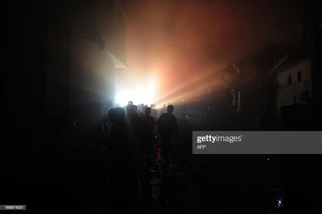 People look on as firefighters attempt to extinguish a blaze at a market in Dhaka on April 7, 2013. More then 100 shops were raized after a fire raced through a market in the middle of the night. AFP PHOTO/Munir uz ZAMAN