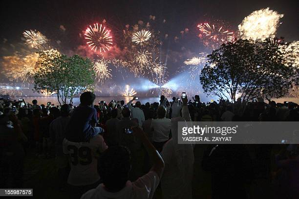 People look on as fireworks light the sky near the Kuwait Towers during celebrations marking the Gulf state's 50th anniversary of its constitution in...
