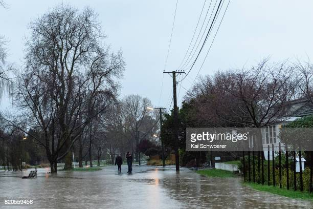 People look on as rising waters cause flooding in Fifield Terrace in the suburb of Opawa on July 22 2017 in Christchurch New Zealand Heavy rain...