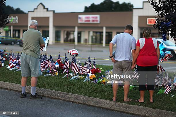 People look on at a memorial setup in front of the Armed Forces Career Center/National Guard Recruitment Office on July 18 2015 in Chattanooga...