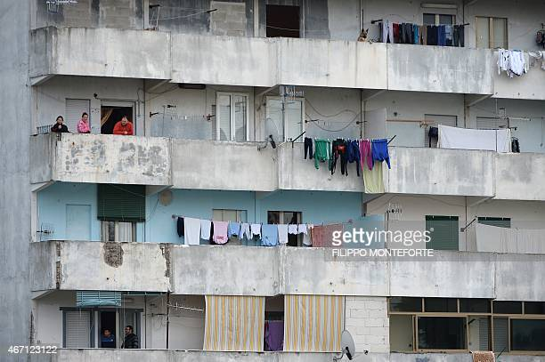 People look on from their balcony during a pastoral visit of Pope Francis in the Scampia district on March 21 2015 in Naples Up to 800000 people are...