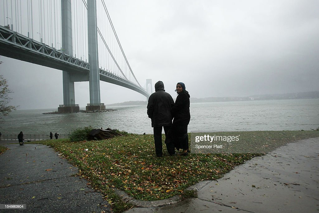 People look out at the Verrazano Bridge as Hurricane Sandy begins to affect the area on October 29, 2012 in the in Brooklyn borough of New York City. The storm, which threatens 50 million people in the eastern third of the U.S., is expected to bring days of rain, high winds and possibly heavy snow. New York Governor Andrew Cuomo announced the closure of all New York City bus, subway and commuter rail service as of Sunday evening.
