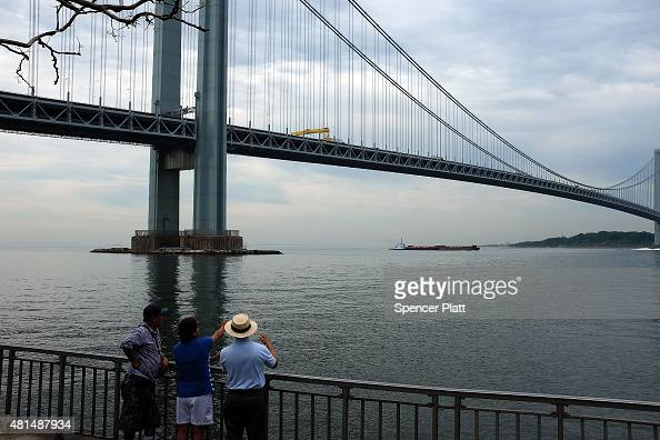 People look out at the Verrazano Bridge from a pedestrian promanade on a sultry morning in Brooklyn on July 21 2015 in New York City Despite an...