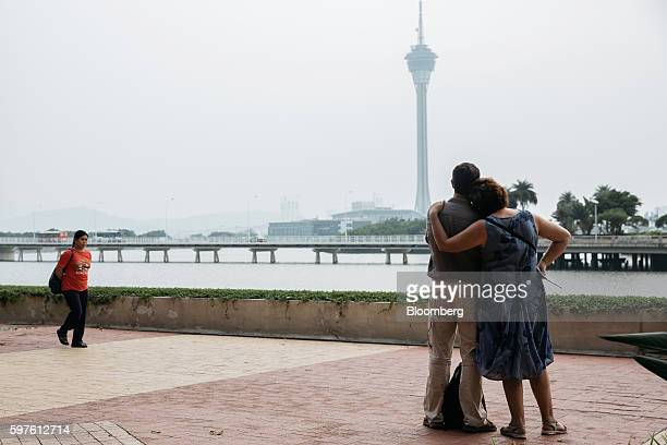 People look out from a lakeshore path near Nam Van Lake as Macau Tower stands in the distance in Macau China on Sunday Aug 28 2016 Macau is scheduled...