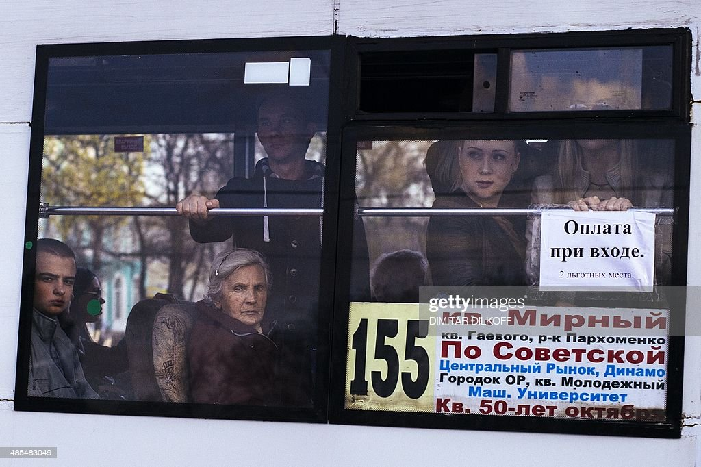 People look out from the window of a bus at demonstrators taking part in a nationalist and pro-unity rally in the eastern Ukrainian city of Lugansk on April 18, 2014. Pro-Russian rebels kept their grip on seized government buildings in Ukraine today, a day after Kiev struck a deal with Russia and the West aimed at easing the crisis in the ex-Soviet republic.