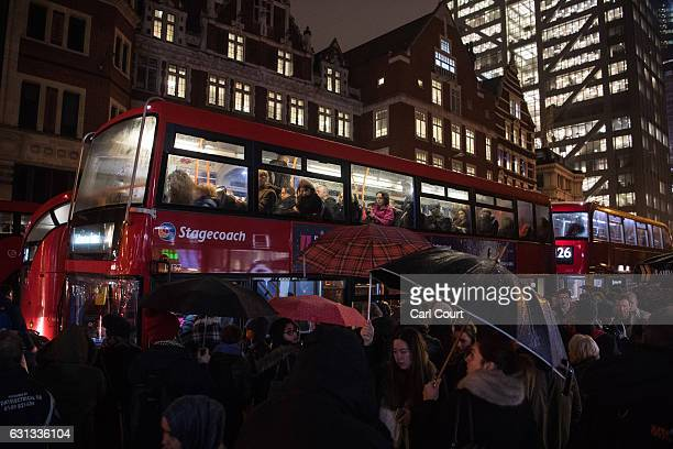 People look out from windows on the top deck of a bus as others queue to board outside Liverpool Street Station on January 9 2017 in London England...