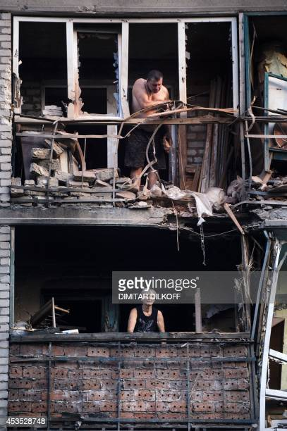 People look out of their damaged flats after shelling in the town of Yasynuvata near the rebel stronghold of Donetsk on August 12 2014 Shelling on a...