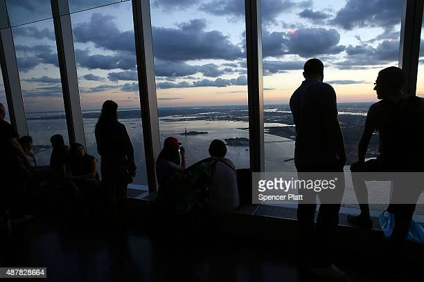 People look out over Manhattan from the observatory at One World Trade Center on September 11 2015 in New York City Throughout the nation today...