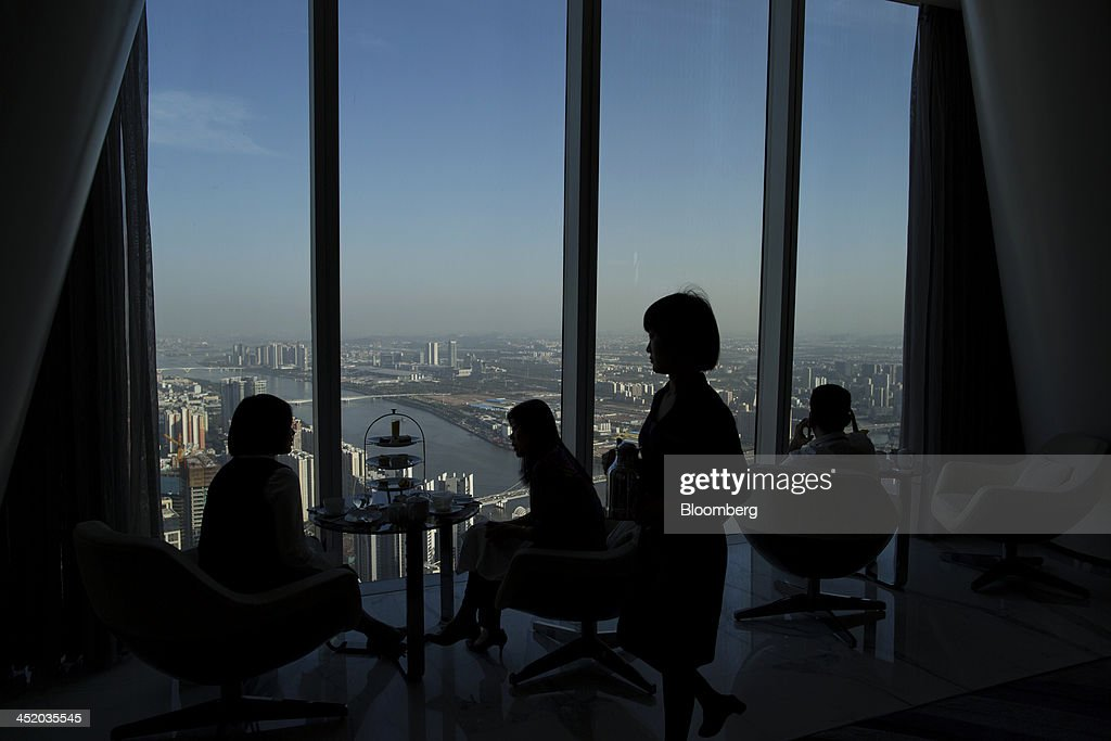 People look out over the city skyline during high tea at The Atrium lounge in the Four Seasons Guangzhou in Guangzhou, Guangdong province, China, on Monday, Nov. 25, 2013. China is proposing the largest package of economic reforms since the 1990s to stoke growth in the worlds biggest emerging market. Photographer: Brent Lewin/Bloomberg via Getty Images