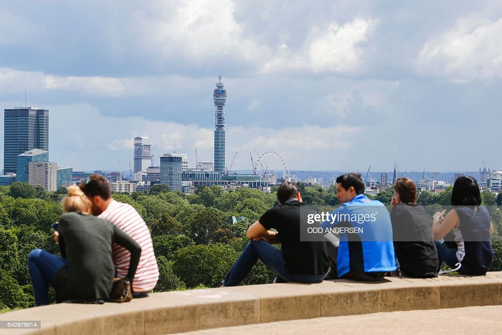 People look out over the skyline of London at landmarks including the BT Tower and the London Eye, from Primrose Hill in north London on June 25, 2016, after the announcement that the UK had voted on June 23 to leave the European Union in a national referendum. The result of Britain's June 23 referendum vote to leave the European Union (EU) has pitted parents against children, cities against rural areas, north against south and university graduates against those with fewer qualifications. London, Scotland and Northern Ireland voted to remain in the EU but Wales and large swathes of England, particularly former industrial hubs in the north with many disaffected workers, backed a Brexit. / AFP / Odd ANDERSEN