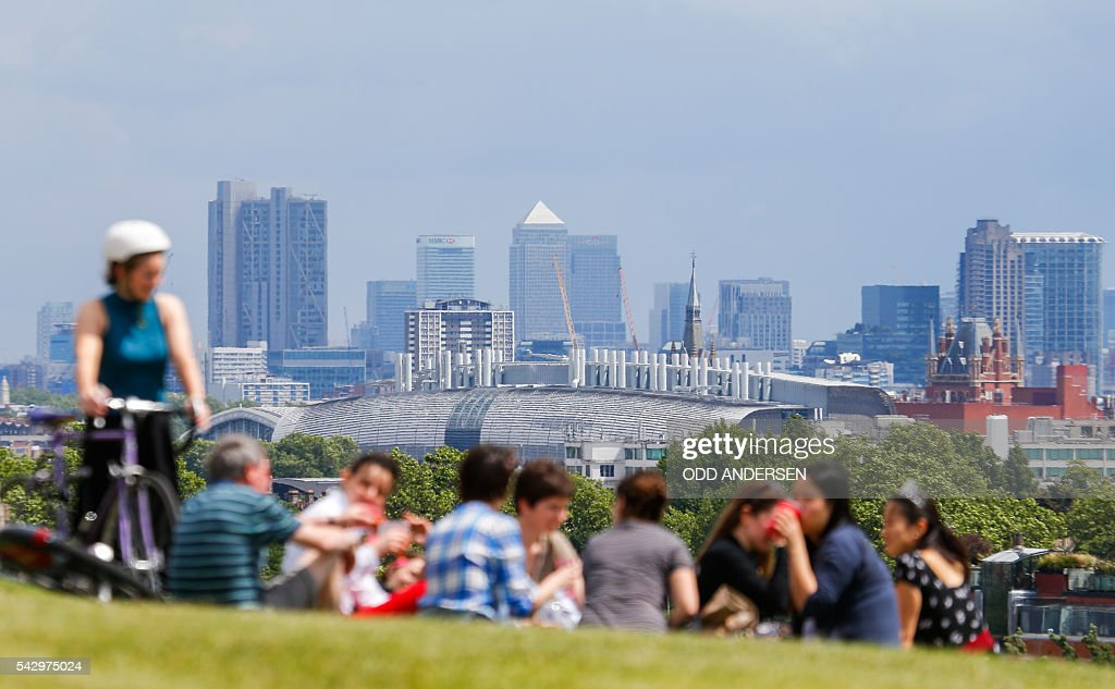 People look out over the skyline of London at landmarks including the Canary Wharf financial district, from Primrose Hill in north London on June 25, 2016, after the announcement that the UK had voted on June 23 to leave the European Union in a national referendum. The result of Britain's June 23 referendum vote to leave the European Union (EU) has pitted parents against children, cities against rural areas, north against south and university graduates against those with fewer qualifications. London, Scotland and Northern Ireland voted to remain in the EU but Wales and large swathes of England, particularly former industrial hubs in the north with many disaffected workers, backed a Brexit. / AFP / Odd ANDERSEN