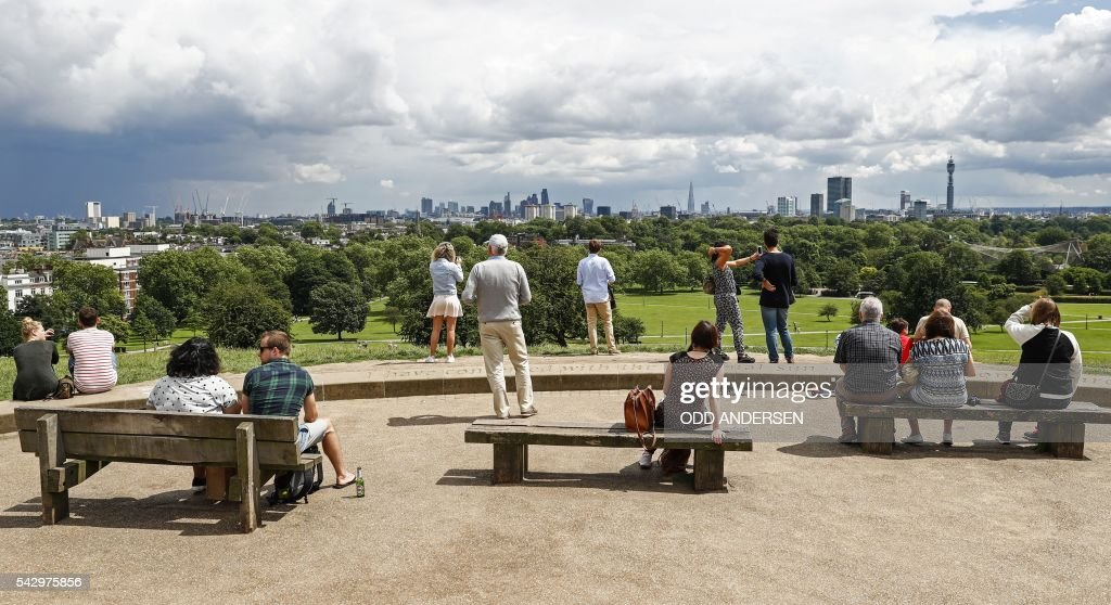 People look out over the skyline of London at landmarks including the BT Tower, the London Eye, and the Shard, from Primrose Hill in north London on June 25, 2016, after the announcement that the UK had voted on June 23 to leave the European Union in a national referendum. The result of Britain's June 23 referendum vote to leave the European Union (EU) has pitted parents against children, cities against rural areas, north against south and university graduates against those with fewer qualifications. London, Scotland and Northern Ireland voted to remain in the EU but Wales and large swathes of England, particularly former industrial hubs in the north with many disaffected workers, backed a Brexit. / AFP / Odd ANDERSEN