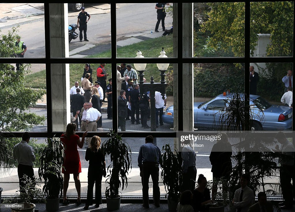 People look out the windows of the Hart Senate Office building during a lock down, on October 3, 2013 in Wasington, DC. The Capitol and the White House were placed on lockdown after an 'active shooter' situation was reported.