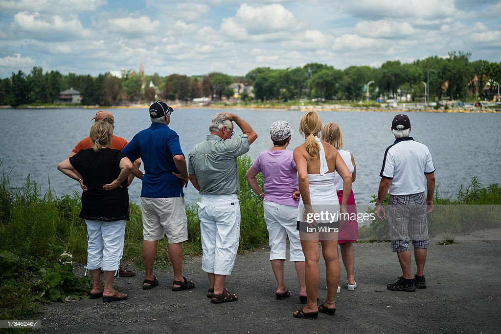 People look out toward the 'red zone' crash site, on July 14, 2013 in Lac-Megantic, Quebec, Canada. A train derailed and exploded into a massive fire that flattened dozens of buildings in the town's historic district, leaving 60 people dead or missing in the early morning hours of July 6.