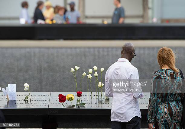 People look over the north memorial pool during the 15th Anniversary of September 11 at the 9/11 Memorial and Museum on September 11 2016 in New York...