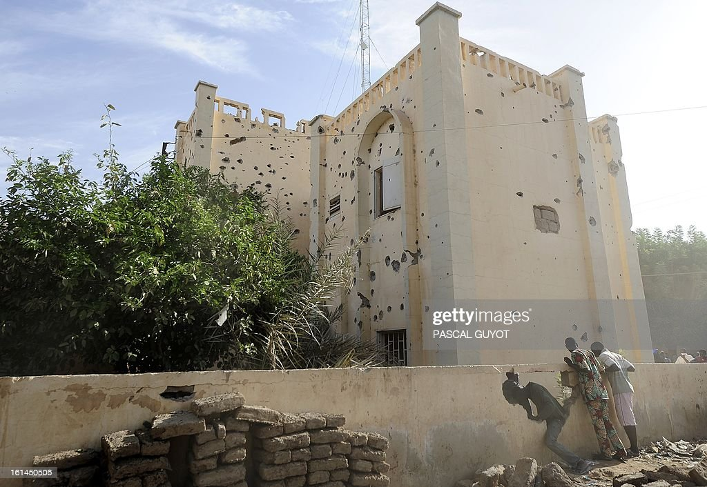 People look over the surrounding wall of a bullet riddled police station one day after Islamist gunmen battled French and Malian troops following two straight days of suicide bombings, on February 11, 2013 in Gao. AFP PHOTO / PASCAL GUYOT