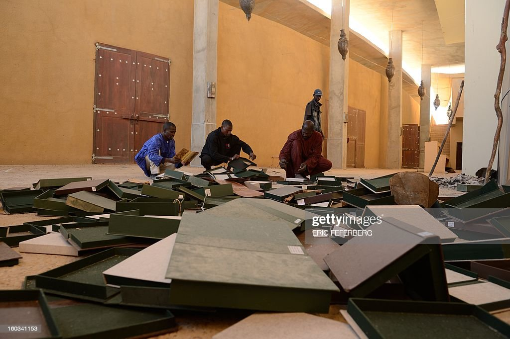 People look through ancient manuscripts at the Ahmed Baba Centre for Documentation and Research in Timbuktu on January 29, 2013. French-led forces seized yesterday Mali's fabled desert city of Timbuktu in a lightning advance north as fleeing Islamists torched a building housing priceless ancient manuscripts. Mayor Ousmane confirmed the fire at the Ahmed Baba Centre for Documentation and Research which housed between 60,000 and 100,000 manuscripts, according to Mali's culture ministry.